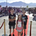 Three students stop for a red carpet photo.