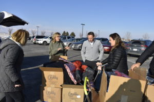 Several Oasis Title Company employees unloading boxes of clothing.