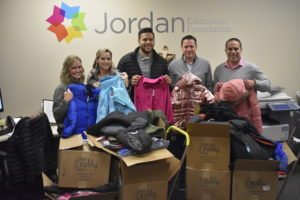 Oasis Title Company employees hold up coat donations.