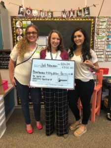 Three people pose with a check.