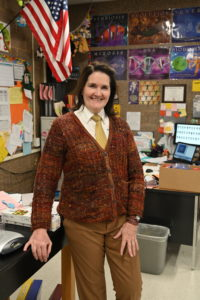A teacher shows off her cardigan.