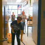 Three custodian cleaning a class room