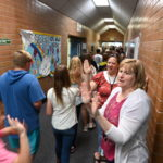 Parents give high fives to students walking down the hall.