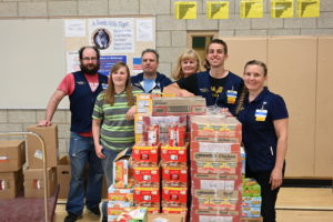 Employees from Walmart stand behind donated food.