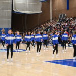 A dance company performs for students.