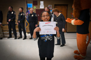 A student holds up her D.A.R.E. graduation certificate.