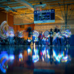 Bingham High Drumline plays in a dark gym.
