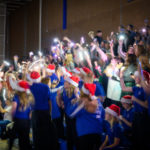 Students in Santa hats cheer in a dark gym.