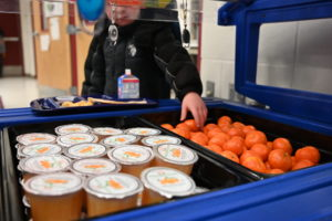 A student grabs an orange from a food cart.