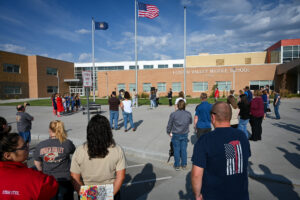 A group watches as students at Hidden Valley Middle School raises the American Flag
