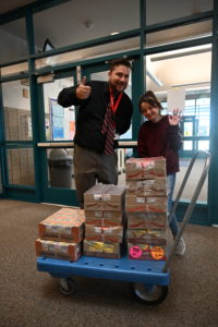 Principal Abram Yospe poses with 6th-grade student Tavia and a cart of food she donated to the school.