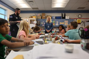 Mayor Dawn Ramsey and a South Jordan Police officer talk with students in a classroom.