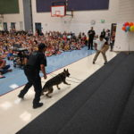 A K9 officer stands ready to show his training to a room full of students.
