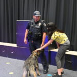 A student talks with a police officer as she pets the K9 officer.