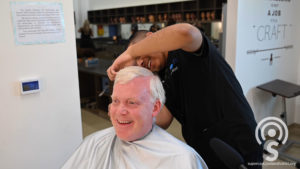 A student give a hair cut to the Superintendent