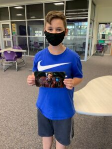Student holds signed autograph from actor Chris Pratt