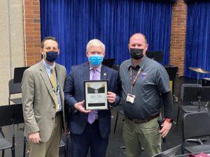 Cody Curtis, Dr. Godfrey and Bryan Leggat hold up an award
