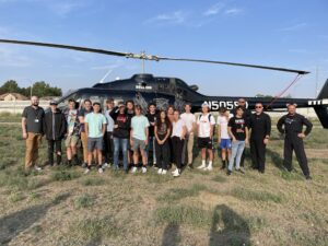 Picture of students with helicopter and pilots