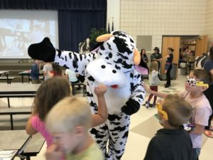 A man in a cow costume gives student high fives.