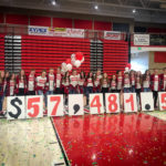 Students hold a sign reading $57,481.