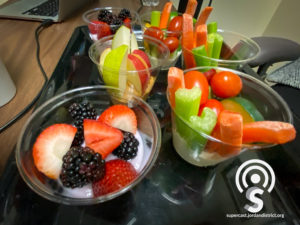 Cups of fruit and vegetables on a table.