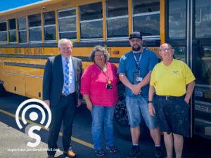 Jordan School District Bus drivers stand next to Dr. Godfrey