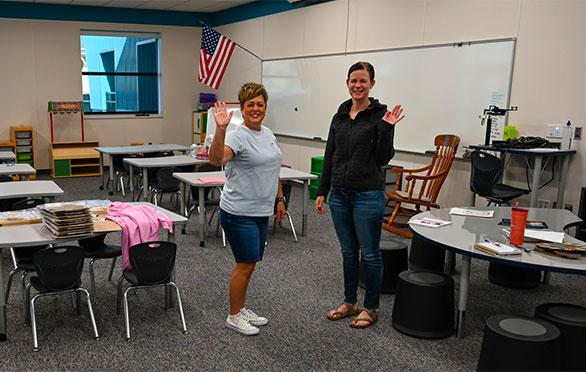 Teachers wave in a classroom