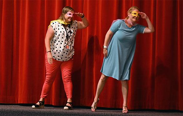 Cherie Wilson & Leslie Ewell on stage in super hero attire
