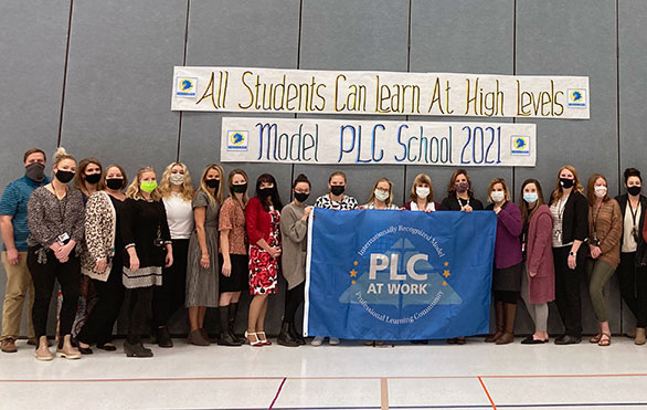 "Staff hold a ""PLC at Work"" flag"