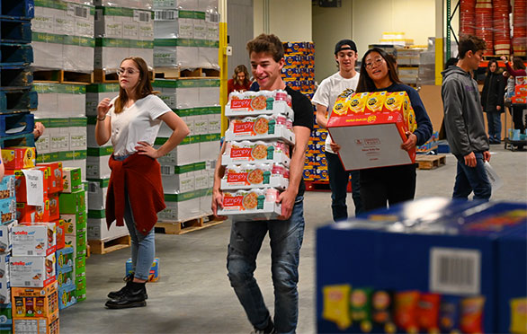 Students moving boxes and cans at the District warehouse