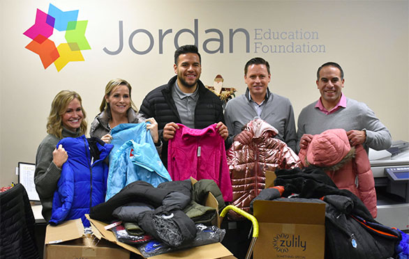 Employees from Oasis Title Company show off donated coats