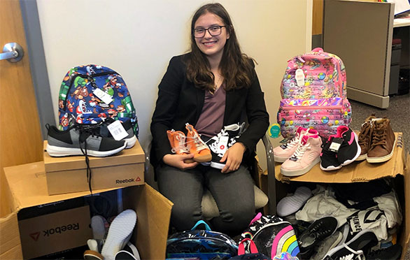 Natalie Smiley with shoe and backpack donations