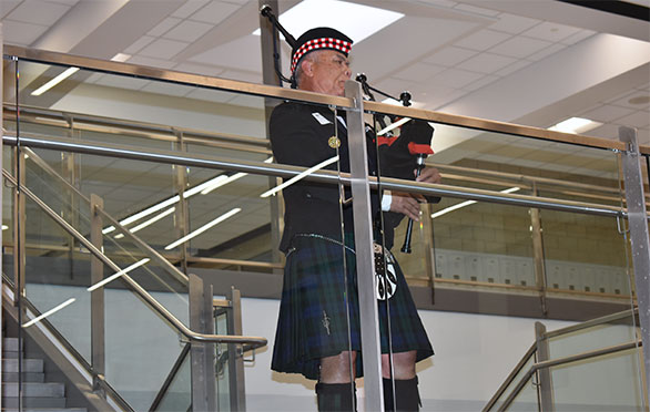 Esera Leota plays bagpipes on the main staircase
