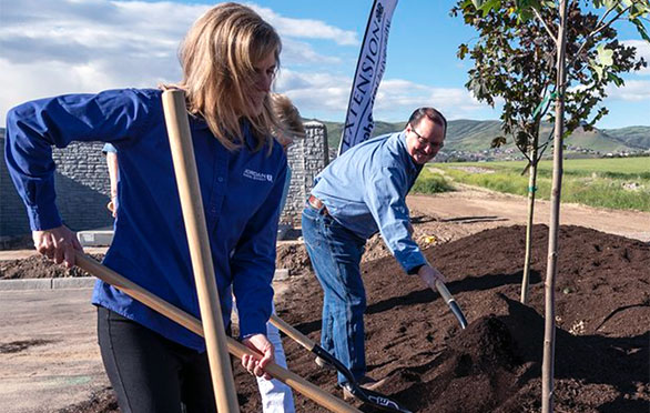Tracy Miller plants a tree in the community
