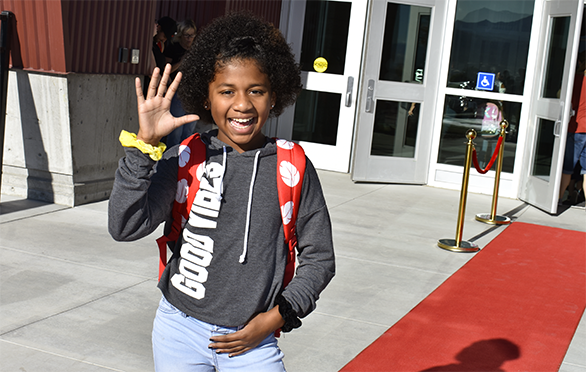 A student wave while on the red carpet at Ridge View Elementary