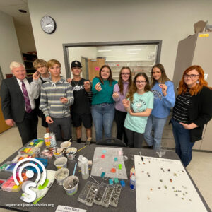 Superintendent stands with jewelry class Students