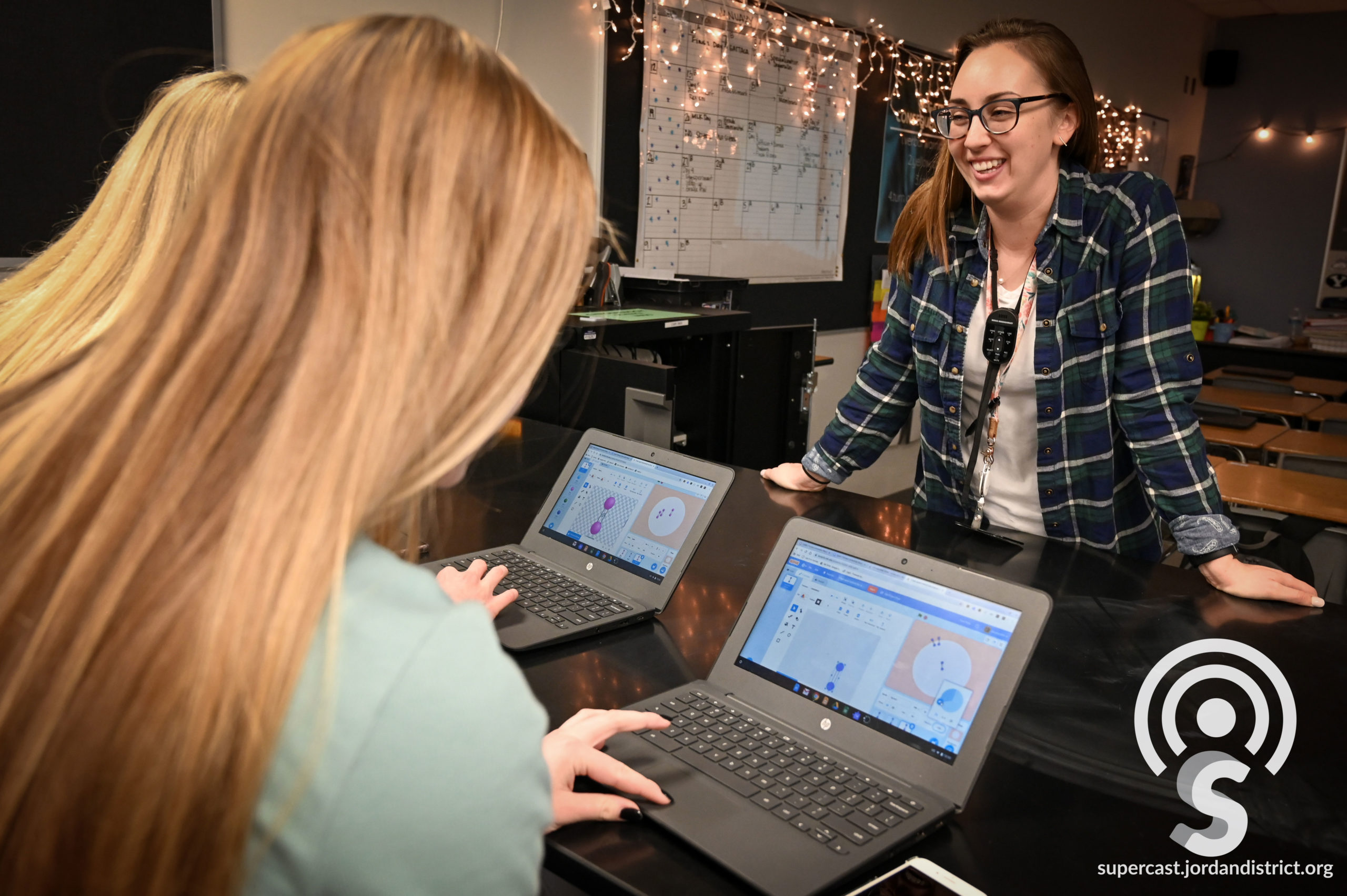 A teacher smiles as she works with two students on laptops