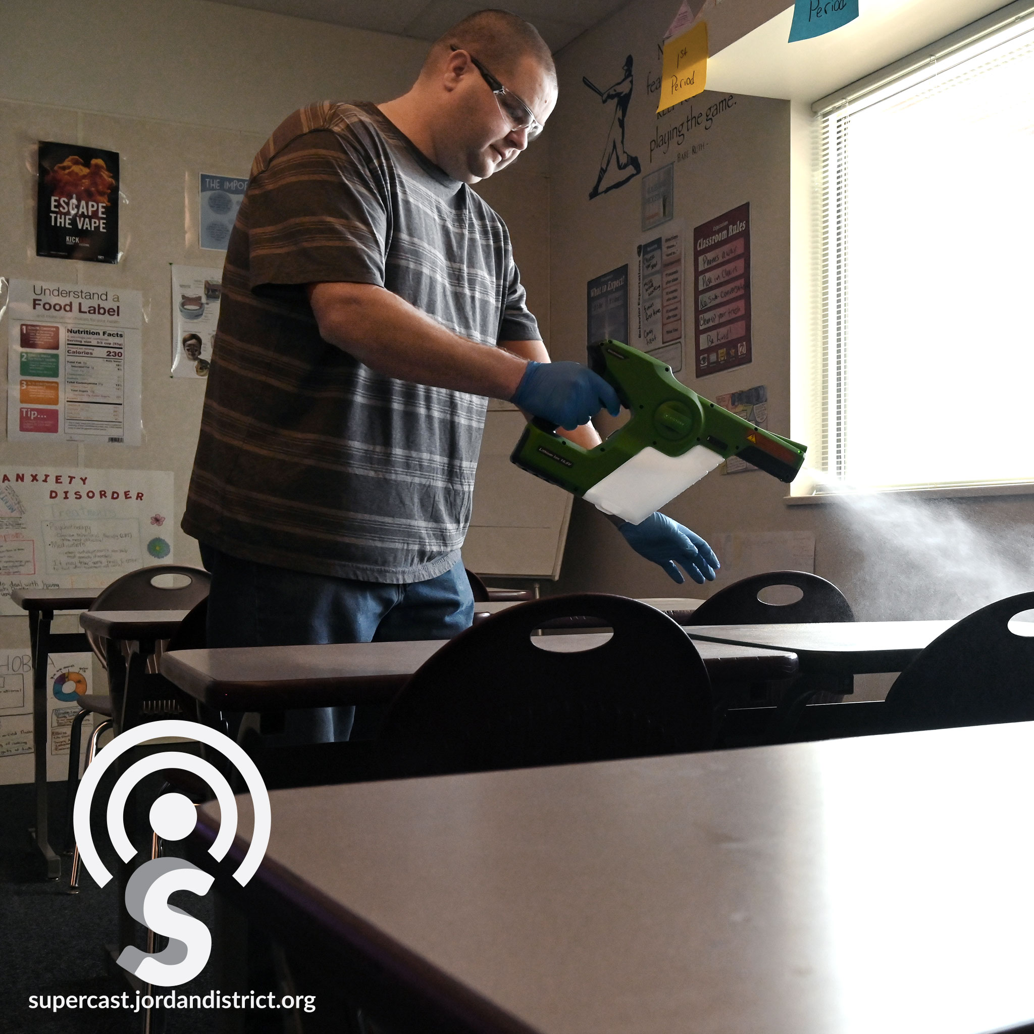 An employee steam cleans a desk in a classroom