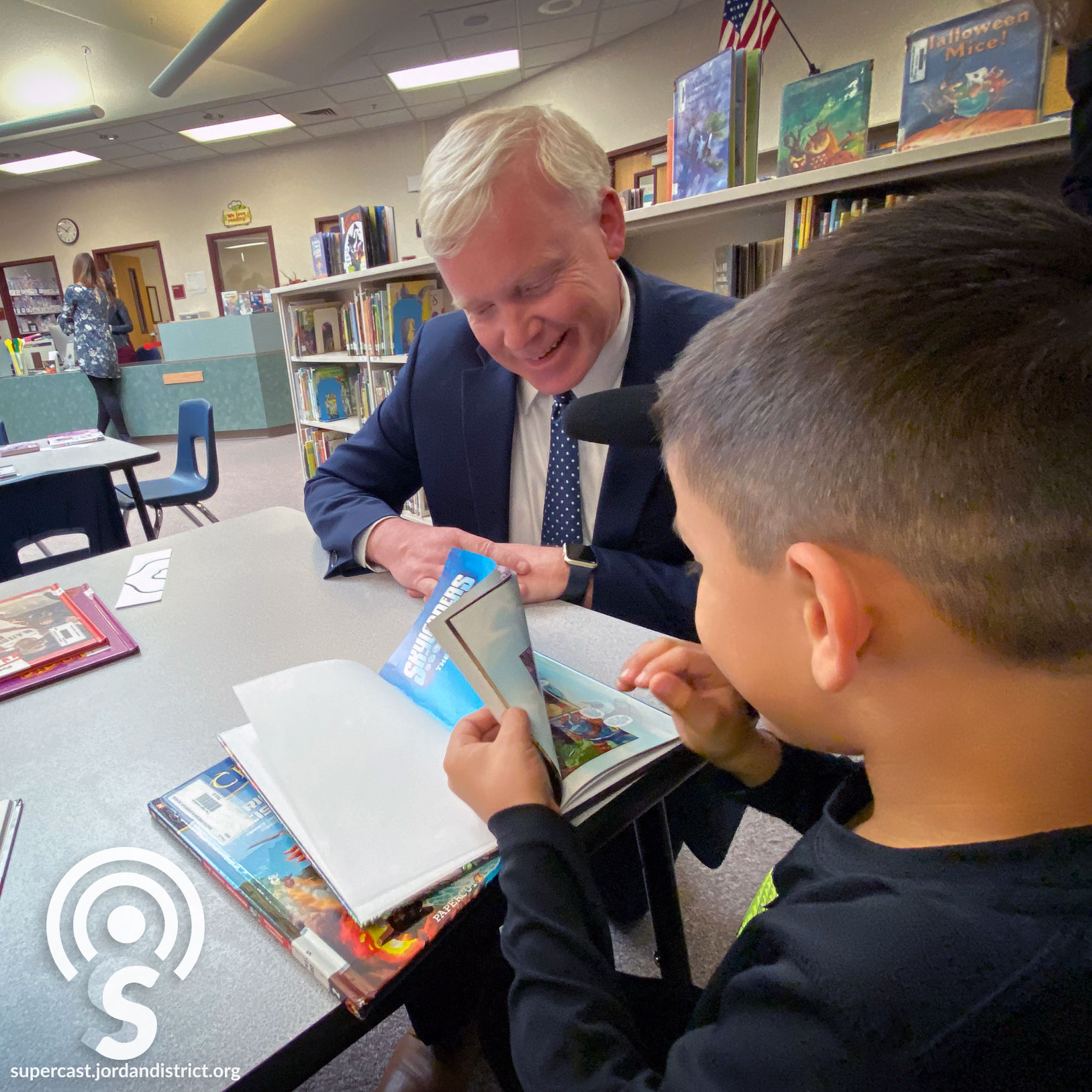Superintendent Godfrey reads with a student