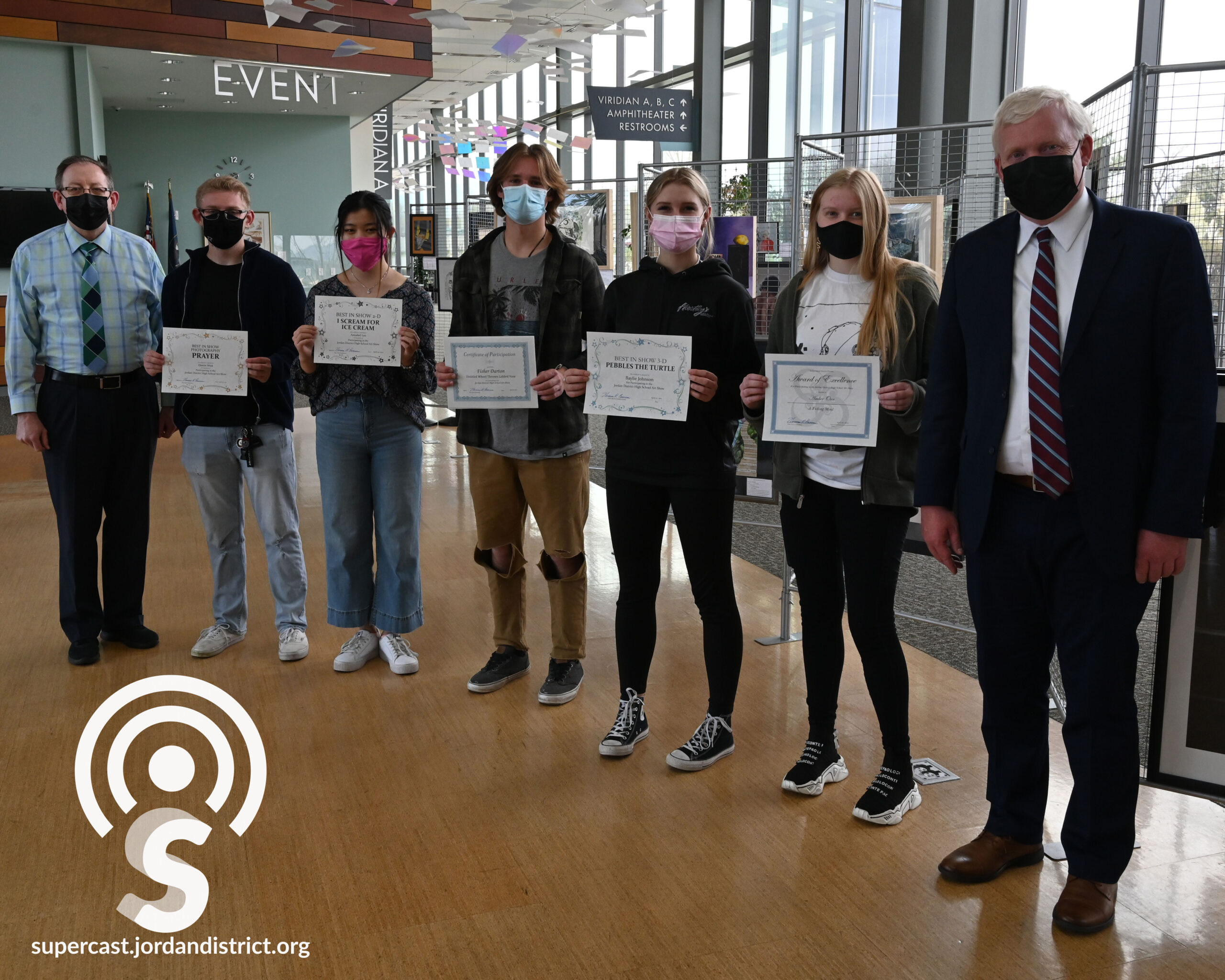 Student artists stand with the Superintendent