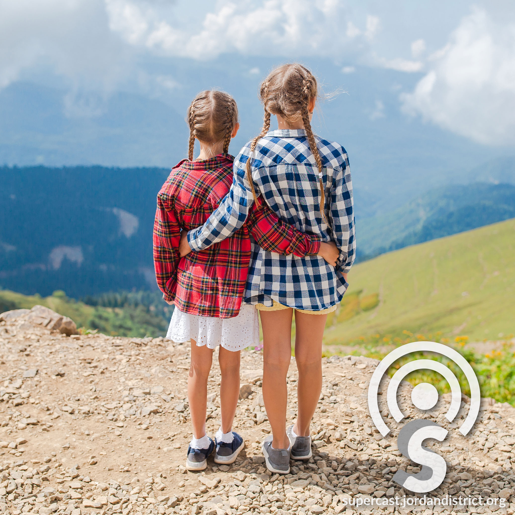 Two girls stare out into the mountain vista