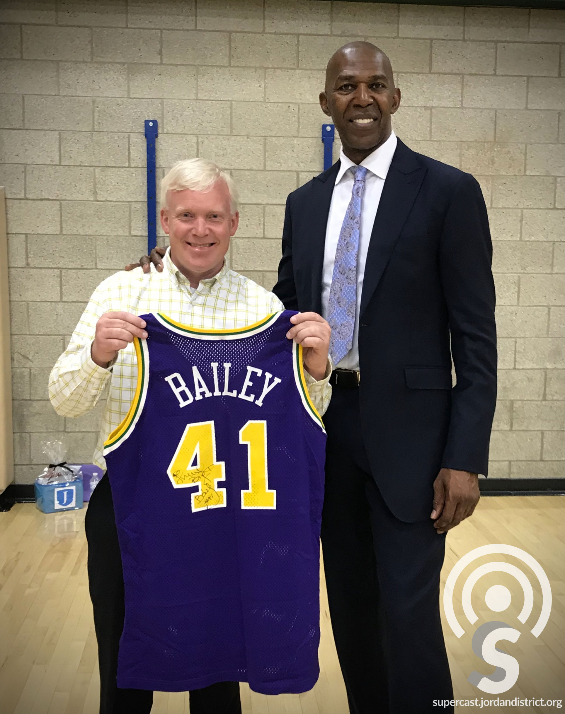 Anthony Godfrey holds Thurl Bailey's #41 Jersey while standing with him