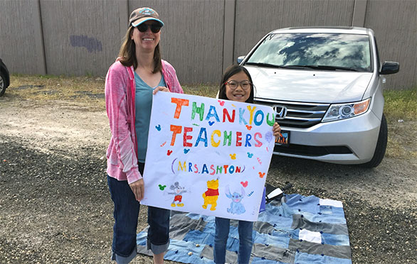 A parent and student display a thank you sign