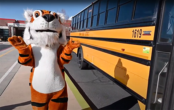 Rory the Tiger talks outside a school bus at Terra Linda Elementary