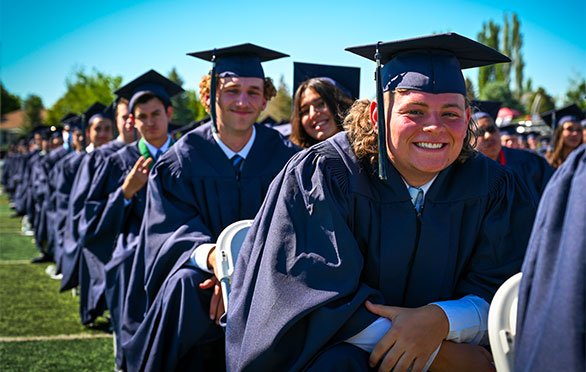 Students smile while waiting for the ceremony to begin