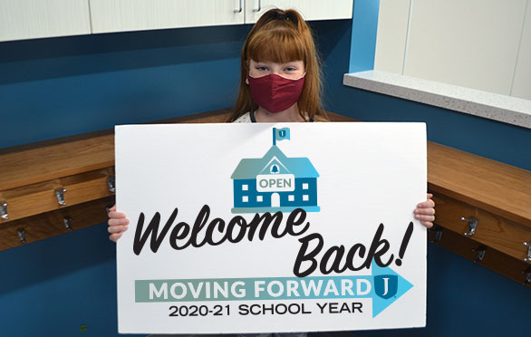 "A student with a ""Welcome Back"" sign"
