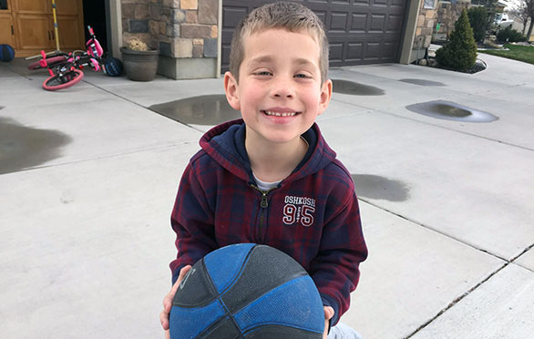 A student plays basketball outside his house