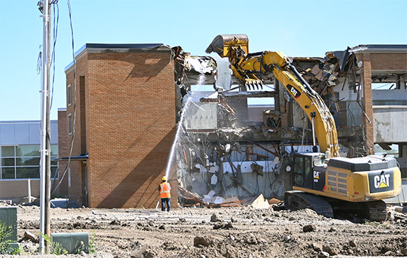 Workers use heavy equipment to tear down the old building